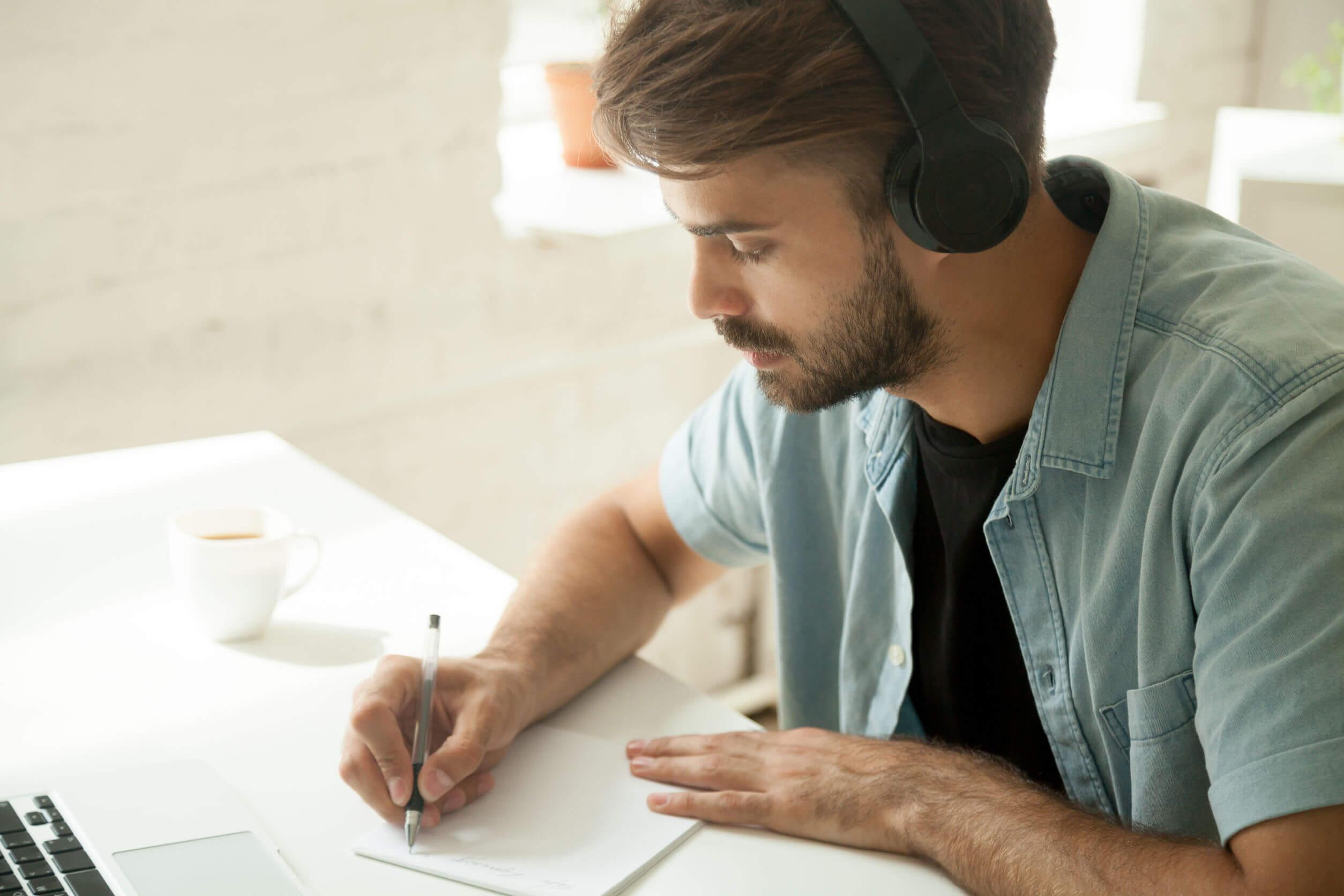 ノートを書く男性